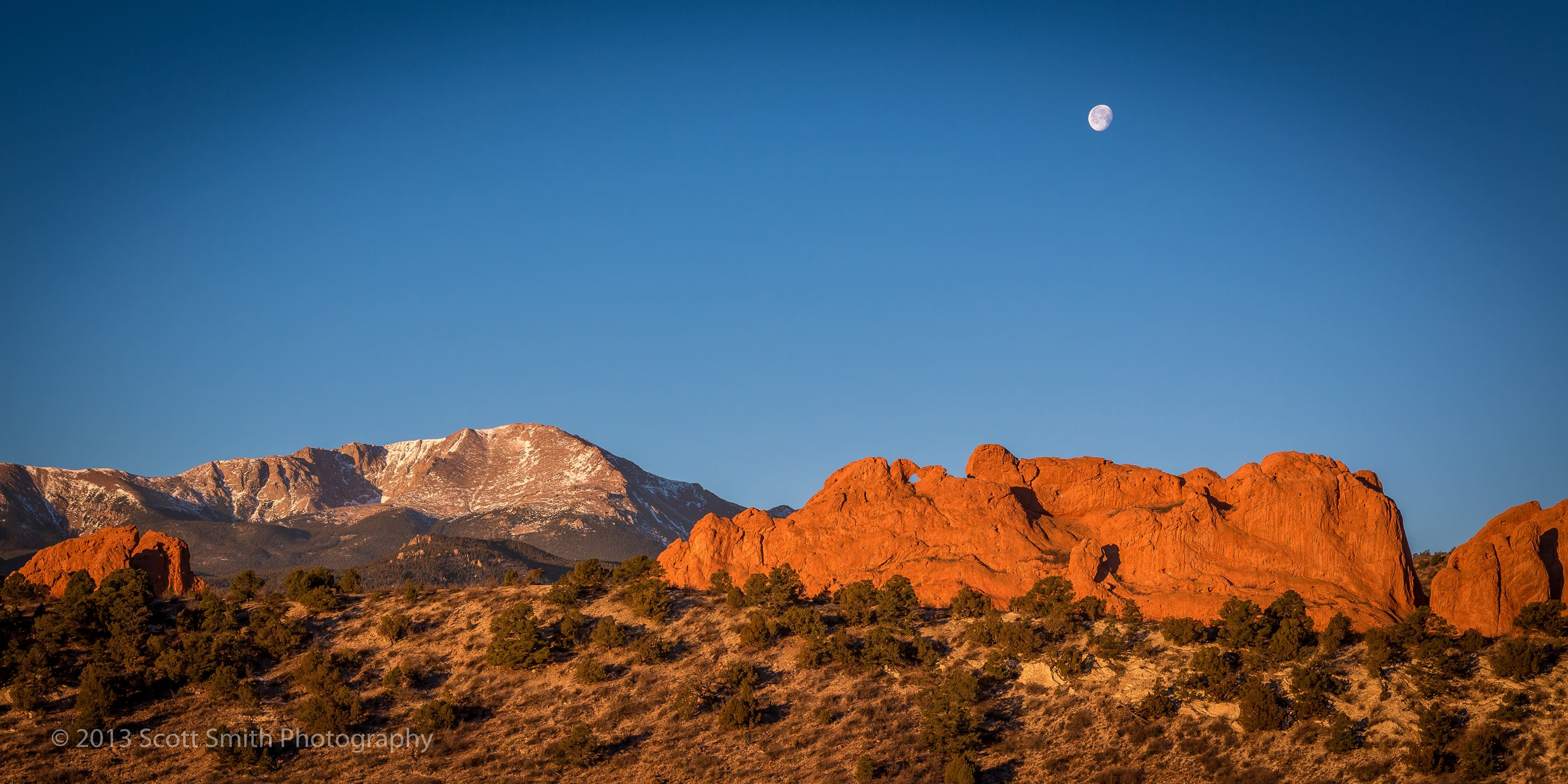 Sun Rising, Moon Setting - The moon sets as the morning sun lights up the Garden of the Gods and Pike's Peak in Manitou Springs, Colorado. by Scott Smith Photos